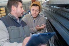 Ingénieur masculin avec l'apprenti vérifiant les niveaux des stocks images libres de droits
