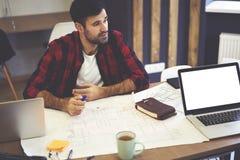 Ingénieur masculin barbu bel pensant tout en dessinant des dépenses graphiques photo libre de droits