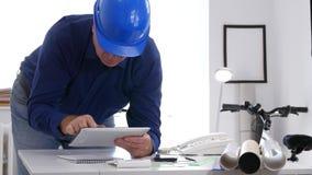 Ingénieur occupé accédant à l'information technique en ligne utilisant le comprimé électronique banque de vidéos
