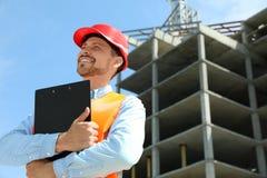 Ingénieur professionnel dans le dispositif de protection avec le presse-papiers au chantier de construction photographie stock