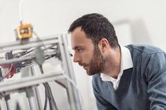 Ingénieur raidi regardant le modèle 3D étant imprimé photo libre de droits