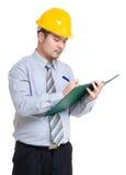 Ingénieur sérieux prenant la note sur le presse-papiers photographie stock libre de droits