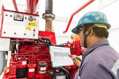 Ingénieur vérifiant le système de contrôle industriel du feu de générateur image stock
