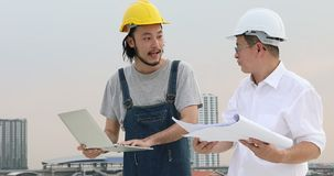 Ingénieurs asiatiques se tenant sur le dessus de toit, jeune carnet d'utilisation d'ingénieur pour discuter au sujet du petit mor banque de vidéos