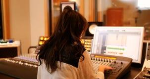 Ingénieurs audio féminins à l'aide du mixeur son clips vidéos