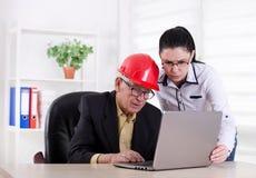 Ingénieurs avec l'ordinateur portable dans le bureau Photographie stock