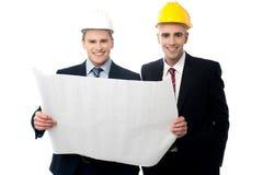 Ingénieurs civils passant en revue le plan de construction Image stock