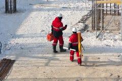 Ingénieurs dans la robe rouge avec un outil sur la construction Image stock