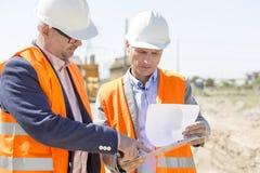 Ingénieurs examinant des documents sur le presse-papiers au chantier de construction contre le ciel clair images stock