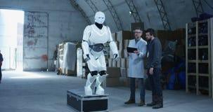 Ingénieurs examinant le robot dans un entrepôt banque de vidéos
