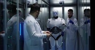 Ingénieurs examinant sur des contrôles de robot photographie stock