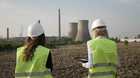 Ingénieurs féminins d'inspecteur examinant des installations de raffinerie de pétrole utilisant le PC de comprimé sur la zone ind banque de vidéos