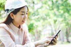 Ingénieurs féminins pressant des téléphones portables photo libre de droits