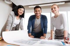 Ingénieurs heureux joyeux se tenant à la table Photo stock