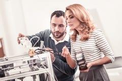 Ingénieurs ingénieux examinant l'imprimante 3D imprimant des dispositions images stock