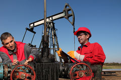Ingénieurs inspectant l'équipement de gisement de pétrole Photos libres de droits