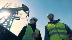 Ingénieurs marchant avec l'ordinateur portable près des tours d'huile, vue inférieure banque de vidéos
