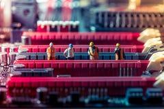 Ingénieurs miniatures réparant la carte Concept de technologie Photographie stock