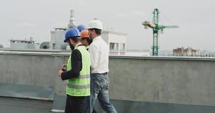 Ingénieurs multi-ethniques attirants architecte et agent de maîtrise marchant sur le dessus de toit du bâtiment moderne de chanti banque de vidéos