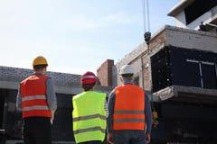 Ingénieurs professionnels dans le dispositif de protection au chantier de construction image stock