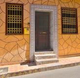 Ing?ng till en bostads- byggnad med en ing?ngsd?rr och f?nster som g?ras i stilen av marockanska konsttraditioner arkivfoto