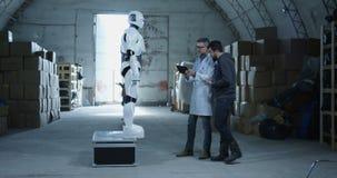 Ing?nieurs examinant le robot dans un entrep?t clips vidéos