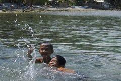 Inga videospel här Filippinungar som har rolig simning i Leyte, Filippinerna, tropiska Asien Arkivfoton