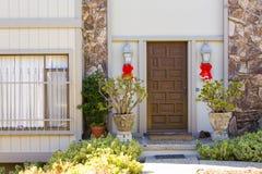 Ingang aan het huis met een houten deur en rotsmuren Stock Foto's