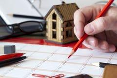 Ingang in de kalender met potlood, kantoorbehoeften en plattelandshuisje Stock Afbeeldingen
