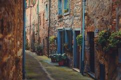 Ingangen aan vlakten in een oud dorp in Toscanië stock foto
