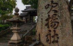 Ingangsstappen en teken van Japans boeddhistisch Fukiage-Heiligdom tijdens een regenachtige dag Imabari, Ehime-Prefectuur, Japan  royalty-vrije stock afbeeldingen