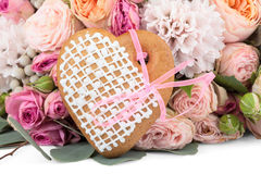 Ingefära hjärta-formad kaka med massor av isolerade blommor Arkivfoton
