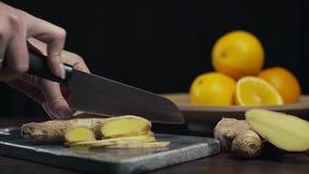 Ingefäran skivas av den skarpa kniven på vaggabrädet, skivor av den nya ingefäran, grönsaker, och vitaminer, vegetarian bantar lager videofilmer