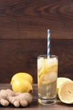 Ingefärsdricka med citronen som accelererar ämnesomsättning Uppfriskande healthful dryck Wood bakgrund arkivfoton
