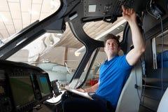 Ingegnere aereo maschio With Clipboard Working nella cabina di pilotaggio dell'elicottero fotografia stock