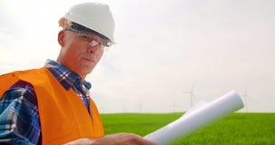 Ingegnere Analyzing Plan While che sta nell'azienda agricola del mulino a vento video d archivio