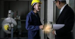 Ingegnere asiatico giovane facendo uso del taccuino per presentare il suo lavoro all'ingegnere di dirigente anziano in fabbrica i stock footage