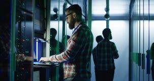 Ingegnere barbuto dell'IT facendo uso del computer portatile nella stanza del server stock footage