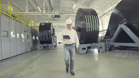 Ingegnere in casco che cammina attraverso la fabbrica video d archivio