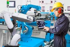 Ingegnere che per mezzo del computer portatile per robot automatico di manutenzione fotografia stock