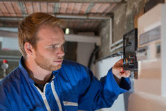 Ingegnere che regola il termostato del sistema di riscaldamento Immagini Stock