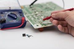 Ingegnere che ripara il circuito elettronico con il multimetro Fotografia Stock
