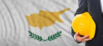 Ingegnere che tiene un casco giallo sul fondo d'ondeggiamento della bandiera del Cipro illustrazione 3D Immagini Stock