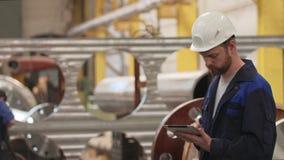 Ingegnere che utilizza compressa ed e sguardo intorno nella fabbrica moderna dell'industria pesante stock footage
