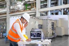 Ingegnere che utilizza computer portatile per la manutenzione nella fabbrica di potere termico fotografie stock