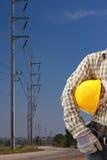Ingegnere con il palo ad alta tensione di elettricità in cielo blu Fotografia Stock