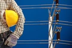 Ingegnere con il palo ad alta tensione di elettricità in cielo blu Fotografie Stock Libere da Diritti