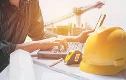 Ingegnere dell'architetto che per mezzo del computer portatile per il lavoro con il casco giallo, Fotografie Stock