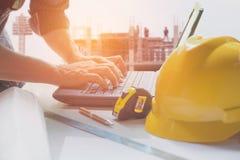 Ingegnere dell'architetto che per mezzo del computer portatile per il lavoro con il casco giallo, Immagine Stock Libera da Diritti