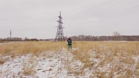 Ingegnere dell'elettricista che va alla linea elettrica sul campo di neve video d archivio